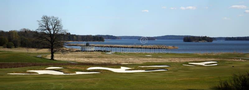 Ένα γήπεδο του γκολφ με τους δρόμους, τις αποθήκες και τις λίμνες και μ στοκ εικόνα με δικαίωμα ελεύθερης χρήσης