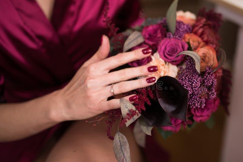 Ένα γαμήλιο δαχτυλίδι στο δάχτυλο της νύφης Όμορφη γαμήλια ανθοδέσμη στο χρώμα marsala στα χέρια της νύφης στοκ εικόνες