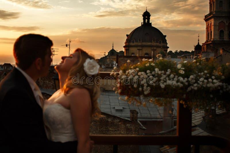 Ένα γαμήλιο ζεύγος στέκεται στη στέγη με το μεγάλο behi αρχιτεκτονικής στοκ φωτογραφία με δικαίωμα ελεύθερης χρήσης