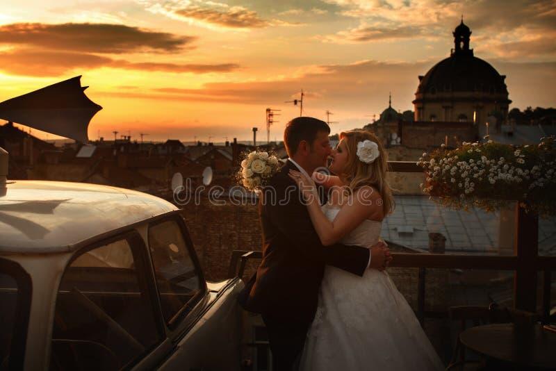 Ένα γαμήλιο ζεύγος φιλά τη στάση κάτω από έναν ουρανό βραδιού στο roo στοκ φωτογραφίες