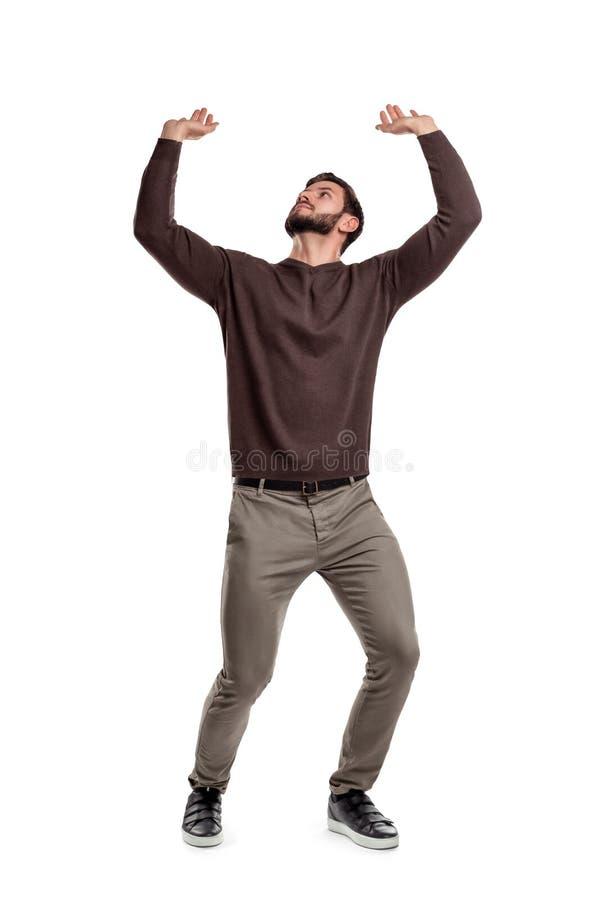 Ένα γενειοφόρο άτομο στα περιστασιακά ενδύματα προσπαθεί να κρατήσει κάτι βαρύ άνωθεν σε ένα άσπρο υπόβαθρο στοκ φωτογραφία