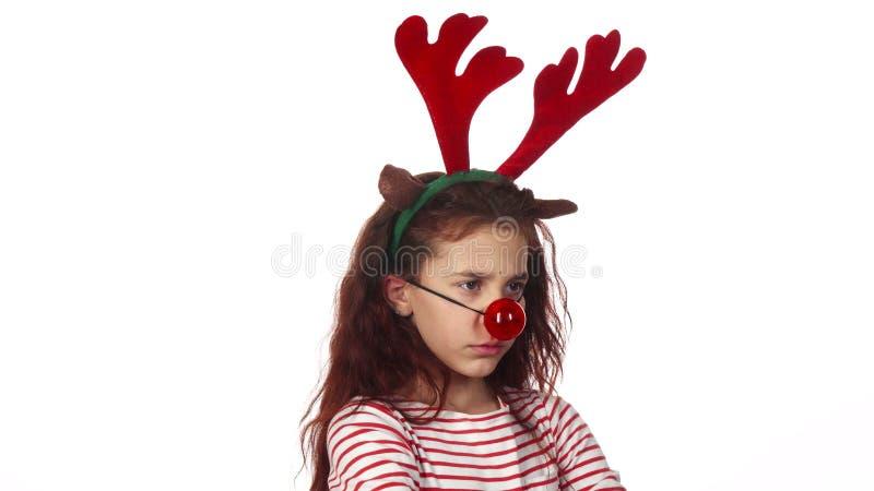 Ένα γλυκό κορίτσι έντυσε σε μια κόκκινη μύτη παιχνιδιών και φαίνεται πολύ αγανακτισμένο στοκ φωτογραφίες με δικαίωμα ελεύθερης χρήσης