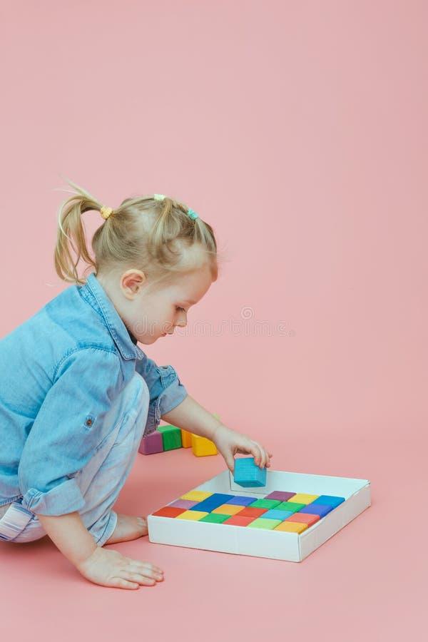 Ένα γοητευτικό μικρό κορίτσι στα ενδύματα τζιν σε ένα ρόδινο υπόβαθρο βάζει τους ξύλινους πολύχρωμους κύβους σε ένα άσπρο κιβώτιο στοκ φωτογραφίες με δικαίωμα ελεύθερης χρήσης