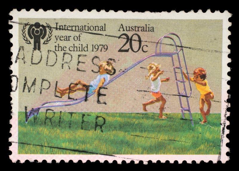 Ένα γραμματόσημο που τυπώνεται στην Αυστραλία παρουσιάζει παιδιά που παίζουν στη φωτογραφική διαφάνεια στοκ φωτογραφίες