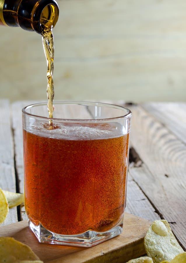 Ένα γυαλί της σκοτεινής έκχυσης μπύρας από το μπουκάλι στοκ εικόνα