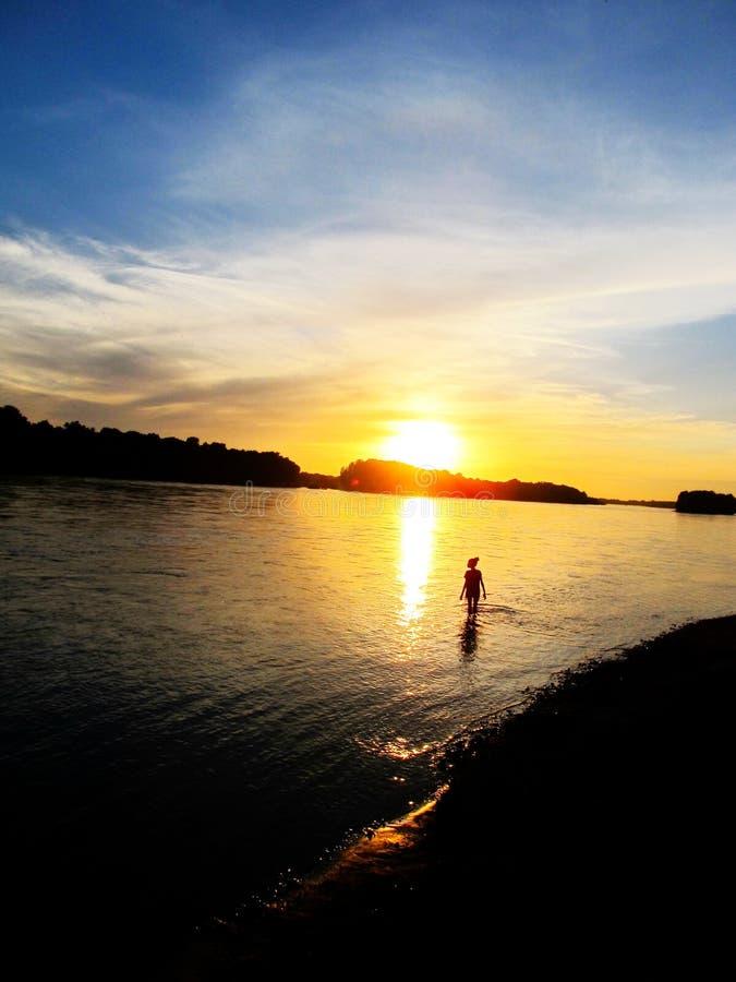 Ένα γυναίκα ή παιδί ανδρών στο νερό στο υπόβαθρο του όμορφου ηλιοβασιλέματος στοκ εικόνες