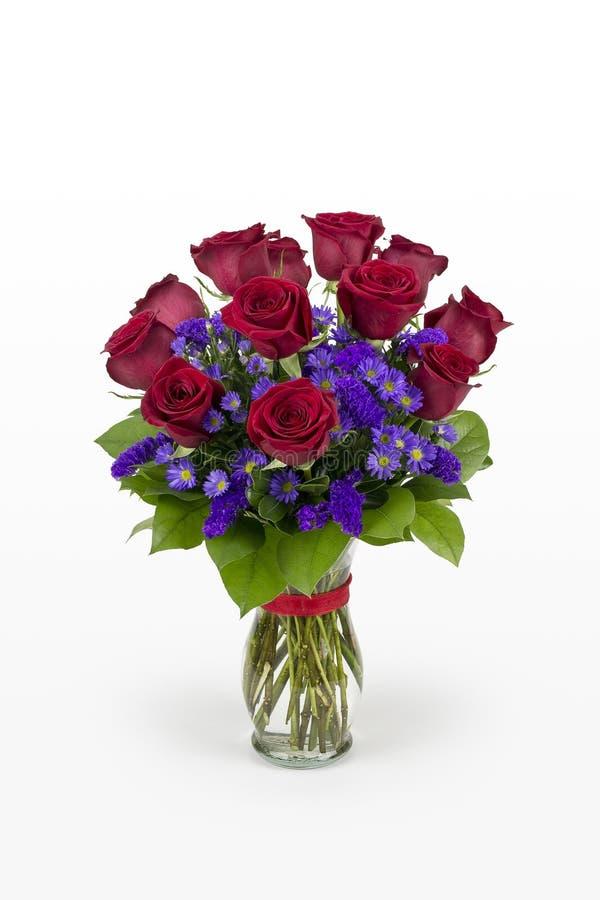 Ένα δωδεκάα κόκκινα τριαντάφυλλα με τα πορφυρά λουλούδια που τακτοποιούνται σε ένα βάζο γυαλιού Ρομαντικό βάζο των τριαντάφυλλων στοκ εικόνα με δικαίωμα ελεύθερης χρήσης