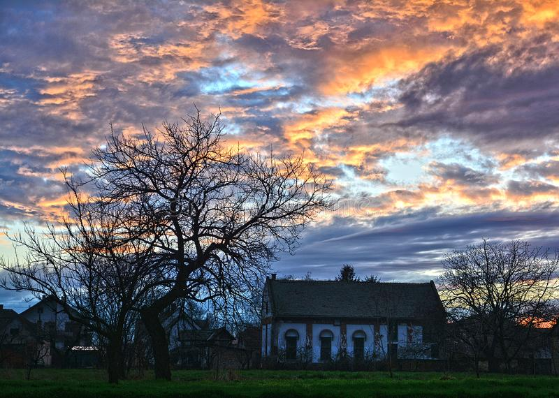 Ένα ειδυλλιακό ηλιοβασίλεμα με ένα δέντρο και το σπίτι στοκ φωτογραφία