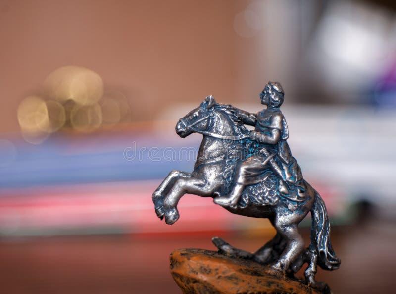 Ένα ειδώλιο ενός στρατιώτη κασσίτερου σε ένα άλογο με το θολωμένο υπόβαθρο στοκ εικόνα