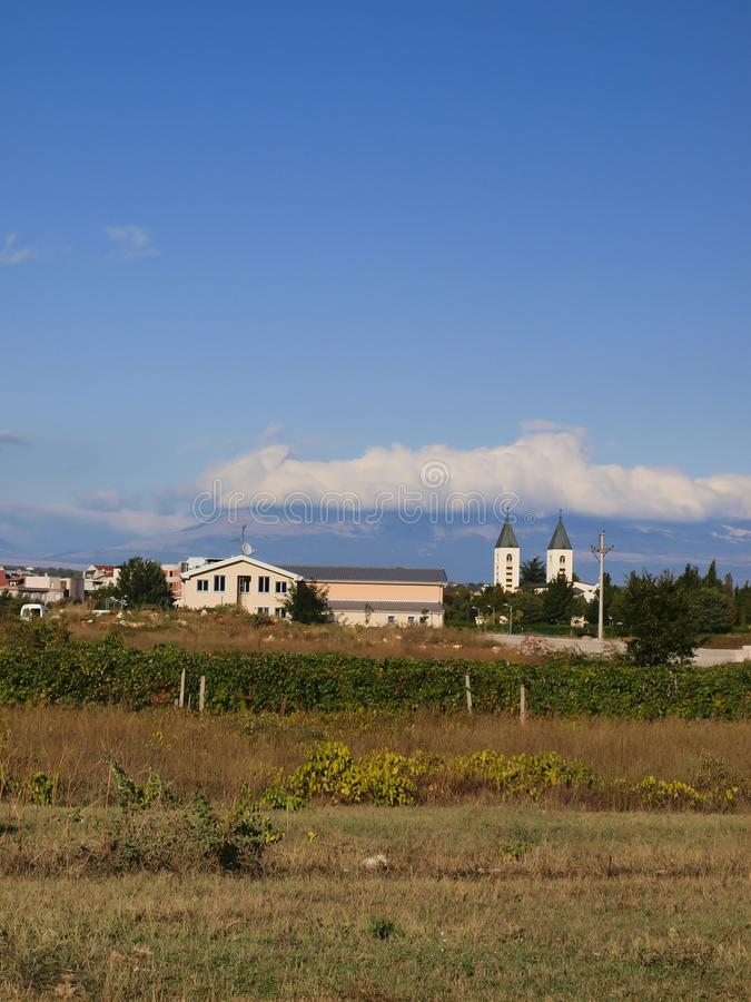 Ένα ειρηνικό τοπίο στην περιοχή Medjugorje, Βοσνία-Ερζεγοβίνη, με τους πύργους της εκκλησίας του ST James στοκ εικόνα με δικαίωμα ελεύθερης χρήσης