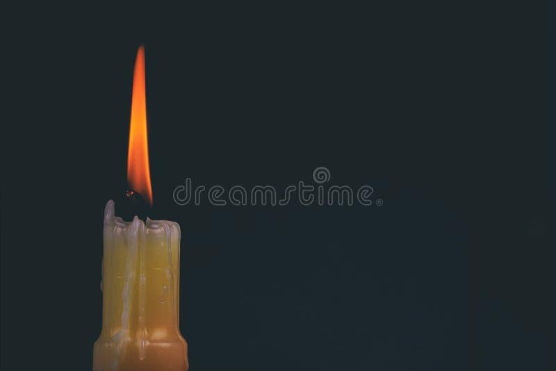 Ένα ελαφρύ αναμνηστικό κάψιμο κεριών λαμπρά στο μαύρο υπόβαθρο στοκ φωτογραφία με δικαίωμα ελεύθερης χρήσης