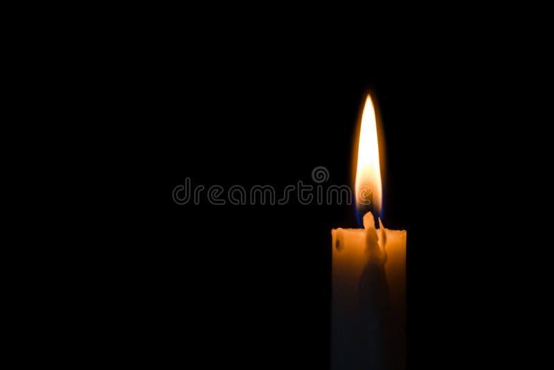 Ένα ελαφρύ κάψιμο κεριών λαμπρά στο μαύρο υπόβαθρο στοκ εικόνες με δικαίωμα ελεύθερης χρήσης