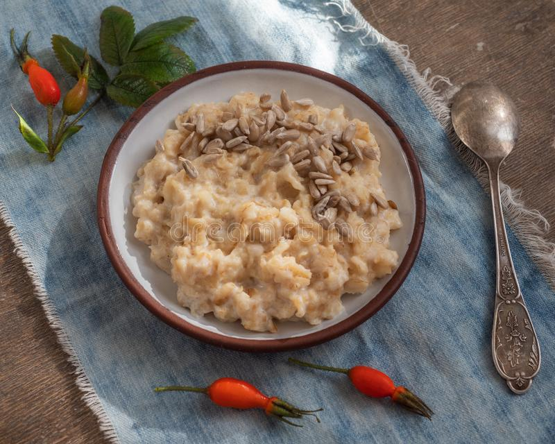 Ένα ελαφρύ πρόγευμα oatmeal του κουάκερ με το γάλα, που εξυπηρετεί σε μια πετσέτα τζιν στον παλαιό πίνακα, τοπ άποψη, άγρια αυξήθ στοκ φωτογραφίες με δικαίωμα ελεύθερης χρήσης