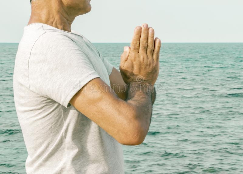 Ένα ενήλικο άτομο που στέκεται με τους φοίνικες σε μια χειρονομία namaste θαλασσίως Η έννοια της πνευματικότητας και self-awarene στοκ φωτογραφία με δικαίωμα ελεύθερης χρήσης