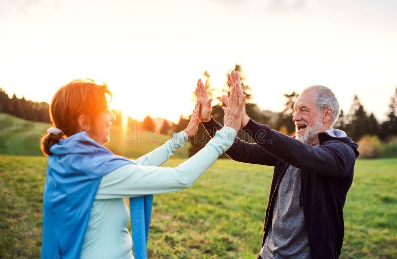 Ένα ενεργό ανώτερο ζεύγος που στηρίζεται μετά από να κάνει την άσκηση στη φύση στο ηλιοβασίλεμα στοκ φωτογραφίες