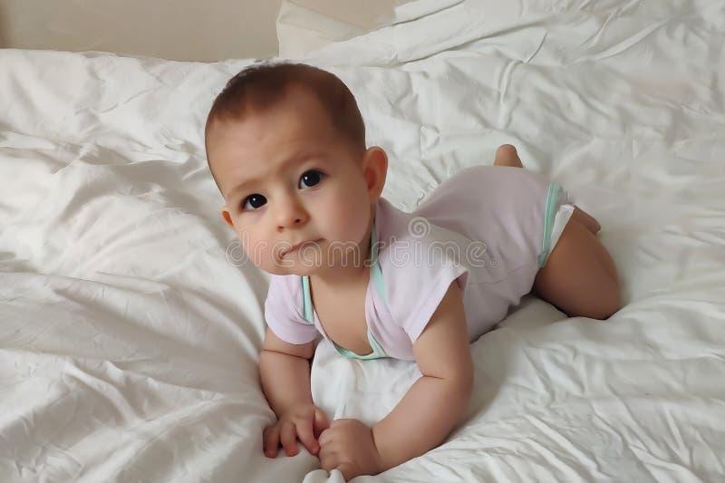 Ένα εξάμηνο παλαιό μωρό σε ανοικτό ροζ σέρνεται στο άσπρο κρεβάτι στοκ εικόνα