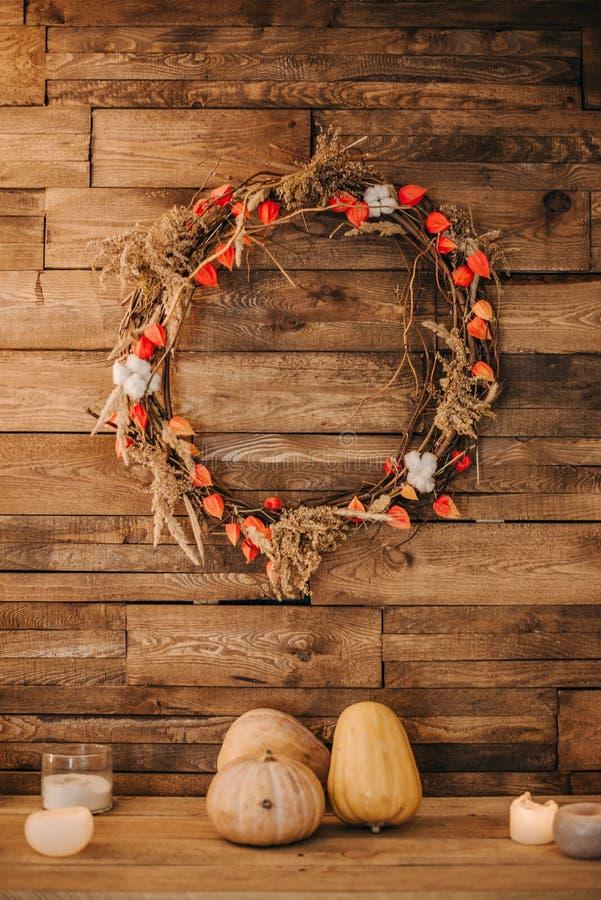 Ένα εορταστικό στεφάνι εξωραΐζει έναν τοίχο του ξύλου με τις κολοκύθες στοκ εικόνες
