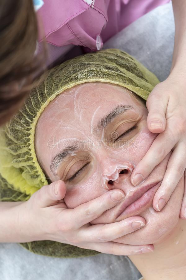 Ένα επαγγελματικό cosmetologist εφαρμόζει μια καλλυντική μάσκα στο πρόσωπο του ασθενή με μια να τρίψει κίνηση με τη βοήθεια των χ στοκ εικόνα με δικαίωμα ελεύθερης χρήσης