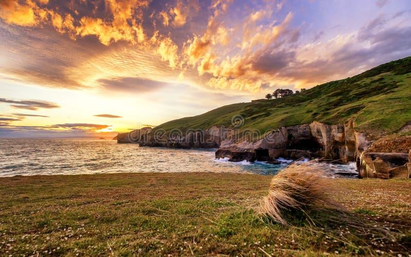 Ένα επικό ηλιοβασίλεμα με το δραματικό κάψιμο καλύπτει στην παραλία σηράγγων Dunedin, Νέα Ζηλανδία στοκ φωτογραφία
