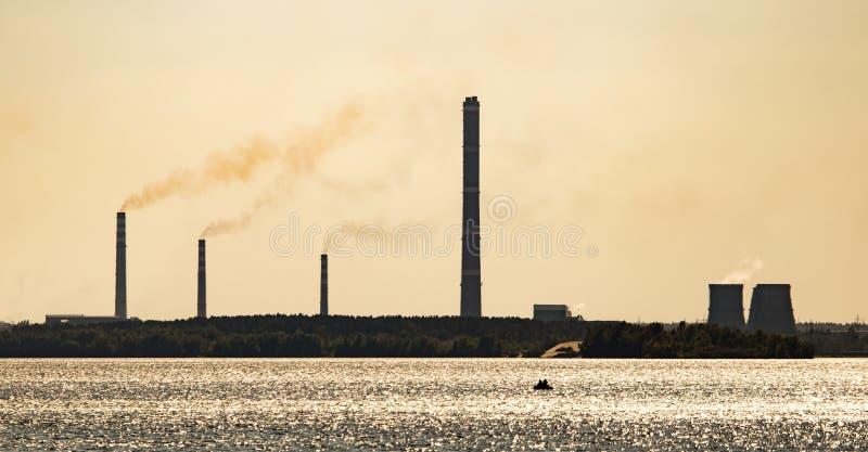 Ένα εργοστάσιο με τους σωλήνες στην ακτή της δεξαμενής στοκ εικόνα