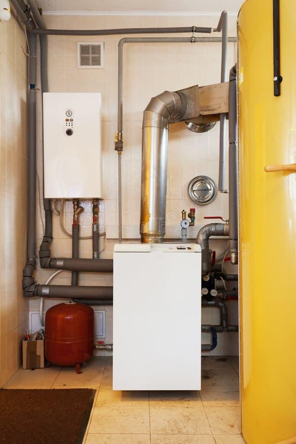 Ένα εσωτερικό δωμάτιο οικιακών λεβήτων με έναν νέο σύγχρονο λέβητα στερεών καυσίμων, ένα ηλεκτρικούς θερμούς υδάτινο σύστημα θέρμ στοκ εικόνες
