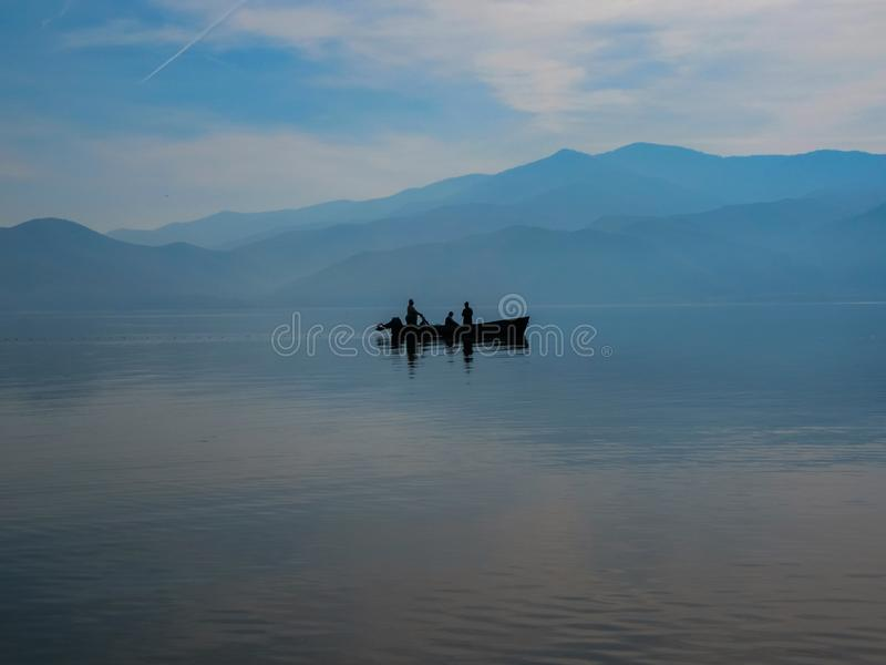 Ένα ευγενές μπλε τοπίο της λίμνης Kerkini με μια βάρκα Σκιαγραφίες Βόρεια Ελλάδα στοκ εικόνες με δικαίωμα ελεύθερης χρήσης