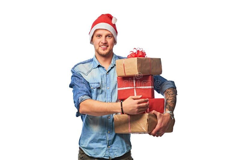 Ένα ευτυχές άτομο που φορά στα κιβώτια δώρων εκμετάλλευσης καπέλων τζιν πουκάμισων και Santa στοκ φωτογραφίες με δικαίωμα ελεύθερης χρήσης