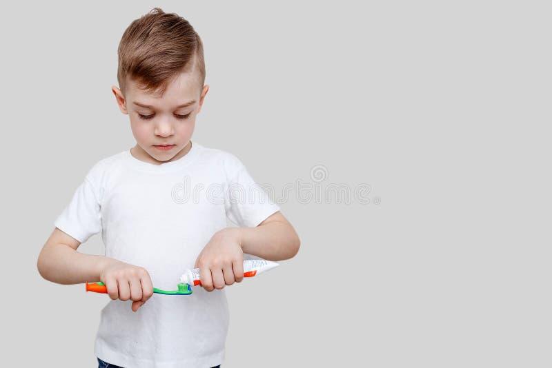 Ένα ευτυχές αγόρι εξάχρονων παιδιών συμπιέζει την οδοντόπαστα επάνω στην οδοντόβουρτσα Οδοντική έννοια υγιεινής στοκ εικόνες