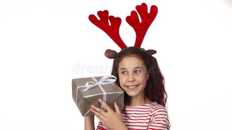 Ένα ευτυχές κορίτσι είναι ευχαριστημένο από το νέο δώρο έτους της στοκ φωτογραφίες