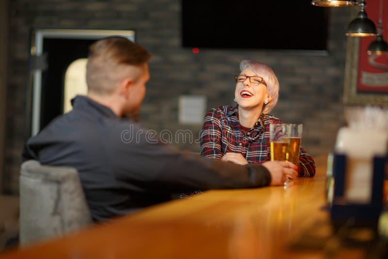Ένα ευτυχές κορίτσι, επικοινωνεί σε έναν φραγμό με ένα άτομο, πίνει την μπύρα και γελά χαρωπά indoors στοκ εικόνες