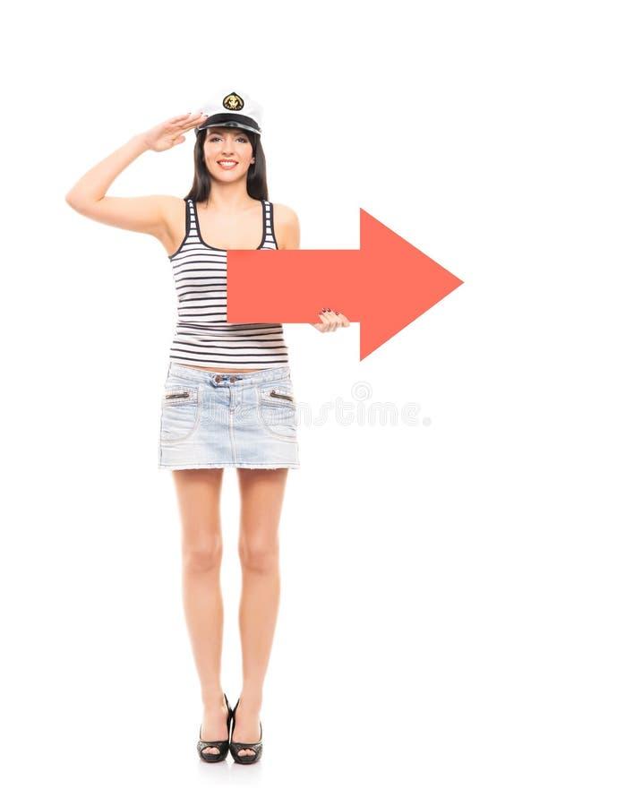 Ένα ευτυχές κορίτσι ναυτικών που κρατά ένα κόκκινο βέλος στο λευκό στοκ εικόνες