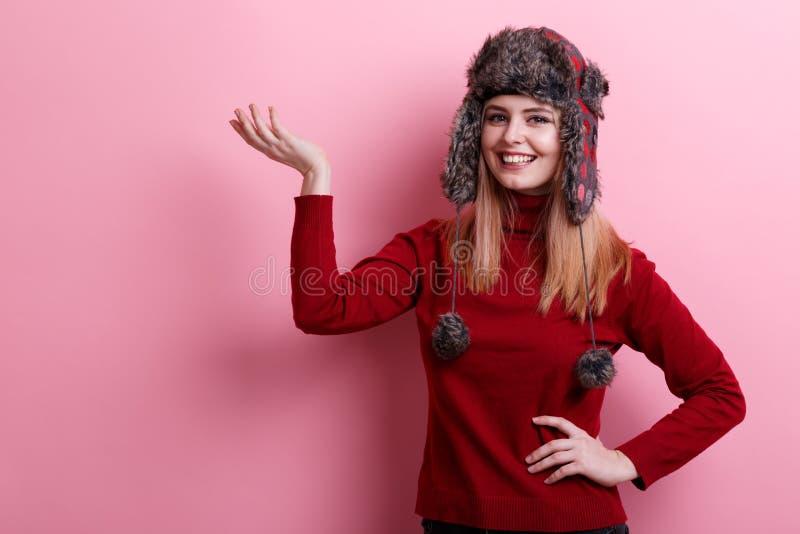 Ένα ευτυχές κορίτσι, σε ένα θερμό καπέλο και τα γλυκά, που χαμογελούν και που κρατούν ένα χέρι στο επικεφαλής επίπεδο Ρόδινη ανασ στοκ φωτογραφία με δικαίωμα ελεύθερης χρήσης
