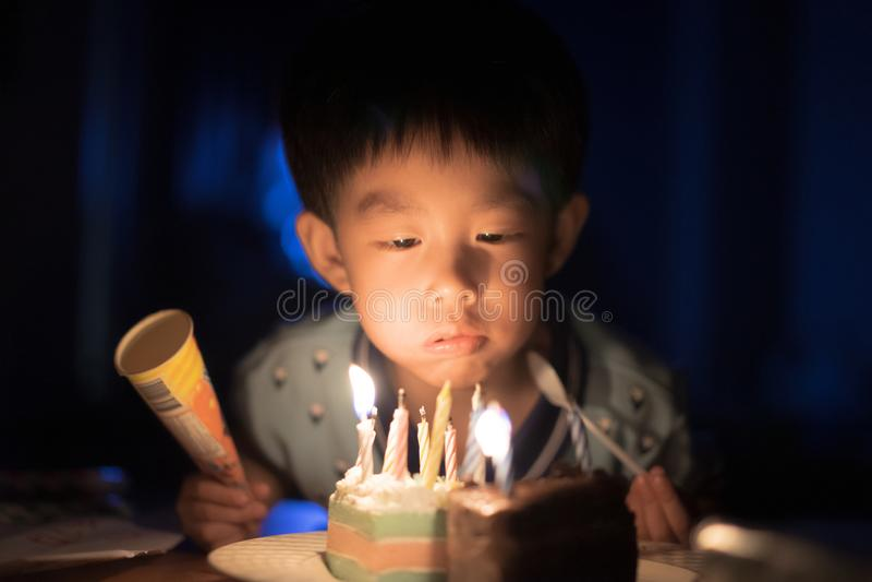 Ένα ευτυχές παιδί φυσά τα κεριά στο κέικ γενεθλίων του στη νύχτα γιορτών γενεθλίων του στοκ εικόνες