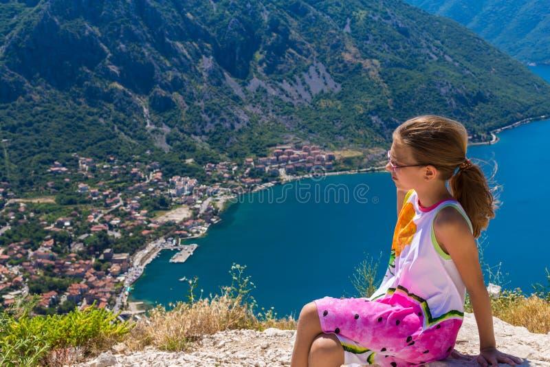 Ένα εφηβικό κορίτσι τουριστών που εξετάζει κάτω τον κόλπο Boka Kotor από μια υψηλή συνεδρίαση απότομων βράχων σε έναν βράχο στοκ εικόνα