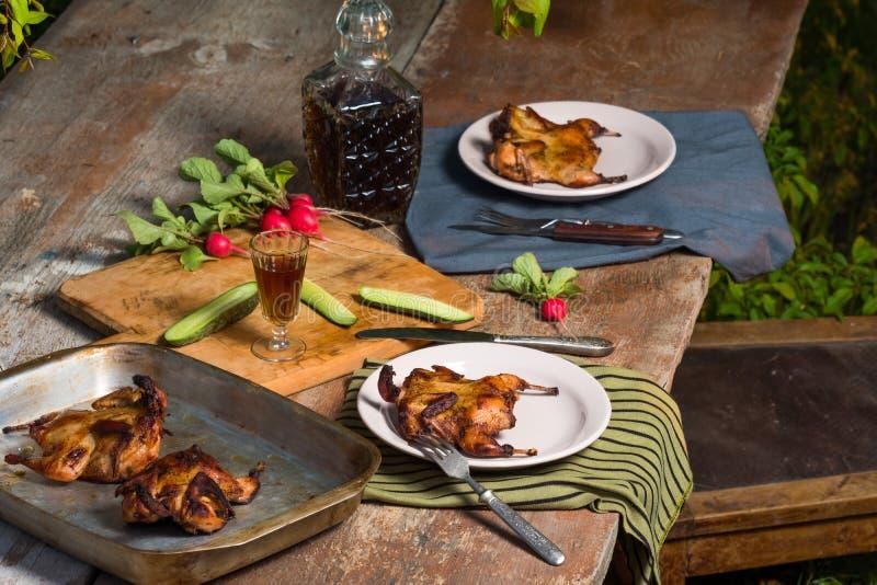 Ένα εύγευστο τηγανισμένο ορτύκι με τα φρέσκα χορτάρια σε έναν ξύλινο πίνακα στον κήπο Αγροτικό ύφος στοκ φωτογραφίες
