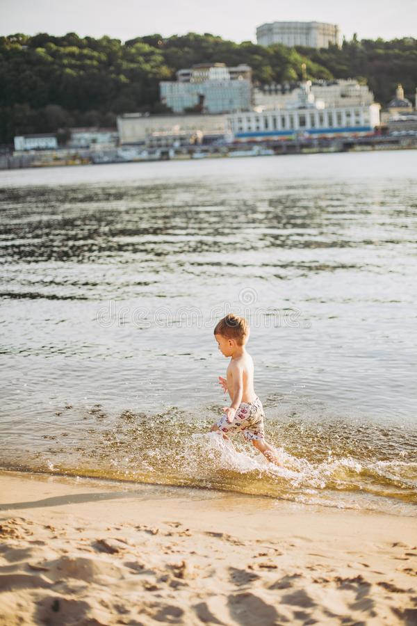 Ένα εύθυμο αγόρι τριών ετών που τρέχουν κατά μήκος της παραλίας κοντά στο νερό και την καταβρέχοντας μύγα Ενεργός αναψυχή το καλο στοκ φωτογραφία με δικαίωμα ελεύθερης χρήσης