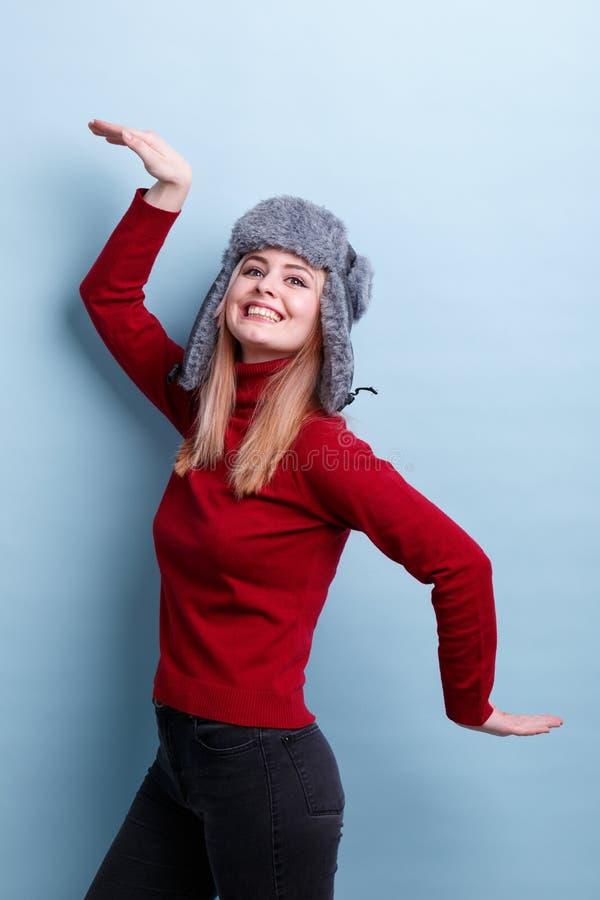 Ένα εύθυμο κορίτσι σε ένα θερμά καπέλο και ένα πουλόβερ, που χορεύουν με τα χέρια και που χαμογελούν ευτυχώς Ένα ξηρό πρόγευμα σε στοκ εικόνες με δικαίωμα ελεύθερης χρήσης