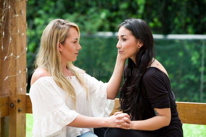 Ένα ζευγάρι της υπερήφανης λεσβιακής συνεδρίασης υπαίθρια να εξετάσει η μια την άλλη και πηγαίνει σε ένα υπόβαθρο κήπων στοκ φωτογραφία