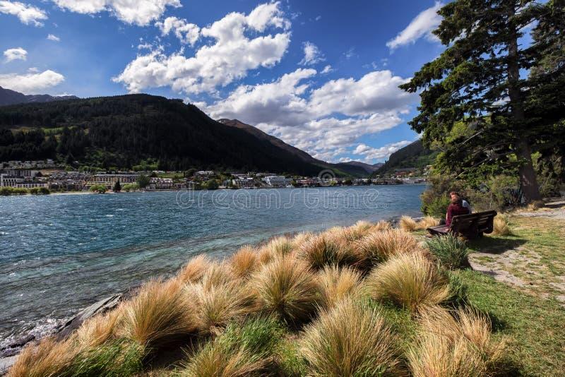 Ένα ζευγάρι του ζεύγους κάθεται στον πάγκο κατά μήκος της όχθης της λίμνης Queenstown, Νέα Ζηλανδία στοκ φωτογραφίες με δικαίωμα ελεύθερης χρήσης