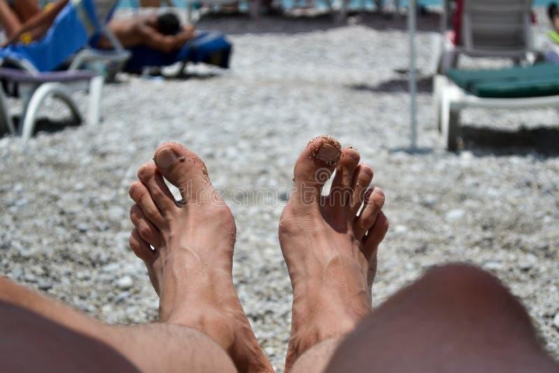 Ένα ζευγάρι των αρσενικών ποδιών Άτομο που στηρίζεται στην παραλία r στοκ φωτογραφίες με δικαίωμα ελεύθερης χρήσης