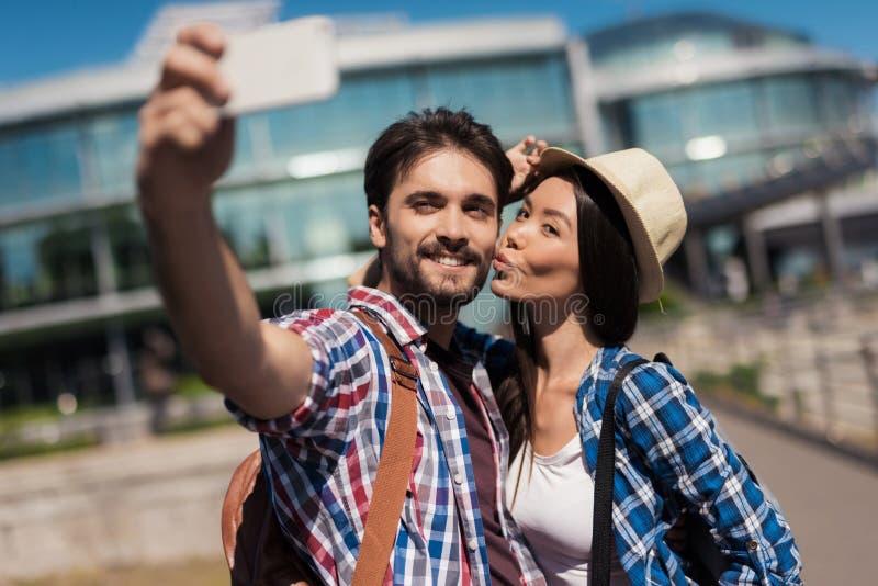 Ένα ζευγάρι των νέων τουριστών κάνει selfie στο υπόβαθρο ενός όμορφου σύγχρονου κτηρίου Το κορίτσι φιλά τον τύπο στοκ εικόνες