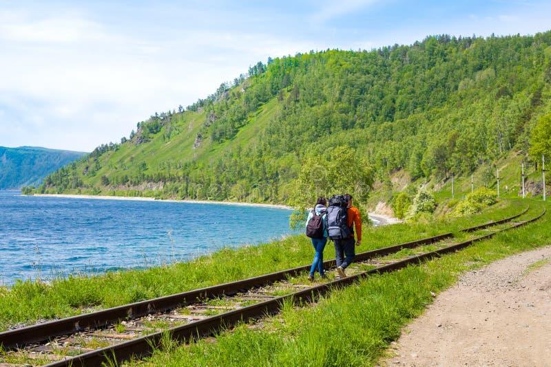 Ένα ζευγάρι των backpackers πηγαίνει κατά μήκος του σιδηροδρόμου circum-Baikal στοκ εικόνα