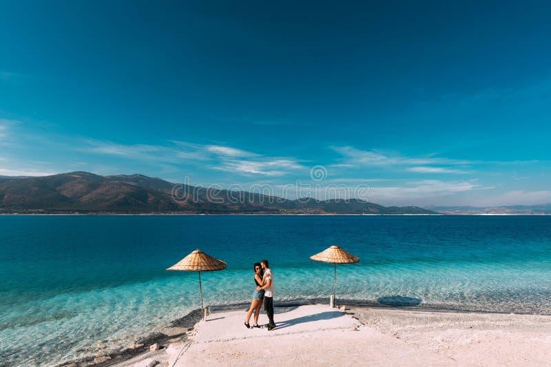 Ένα ζεύγος ερωτευμένο εξετάζει την μπλε λιμνοθάλασσα θερινό ηλιοβασίλεμα αγάπης βραδιού ζευγών παραλιών εραστές μήνα του μέλιτος στοκ εικόνα