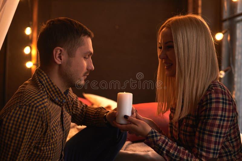 Ένα ζεύγος ερωτευμένο εξετάζει το ένα το άλλο ευτυχώς και κρατά ένα καίγοντας κερί στοκ εικόνες