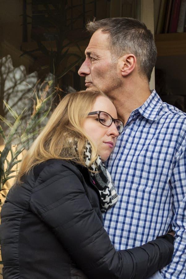 Ένα ζεύγος με ένα ονειροπόλο βλέμμα που αγκαλιάζει το ένα το άλλο στοκ εικόνα