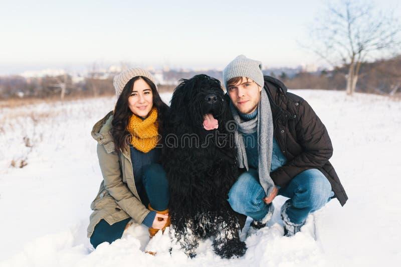 Ένα ζεύγος που απολαμβάνει το χειμώνα περπατώντας το μεγάλο μαύρο havin σκυλιών τους στοκ εικόνα με δικαίωμα ελεύθερης χρήσης