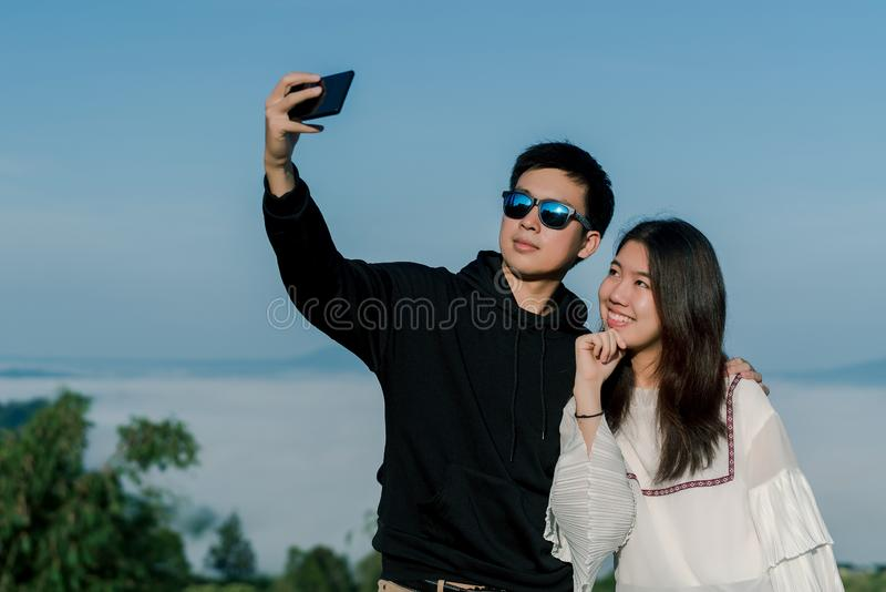 Ένα ζεύγος που είναι εραστές στη χρονολόγηση παίρνει selfies μαζί από το smartphone με τη τοπ άποψη του λόφου στο backgroud Ένα α στοκ εικόνες με δικαίωμα ελεύθερης χρήσης