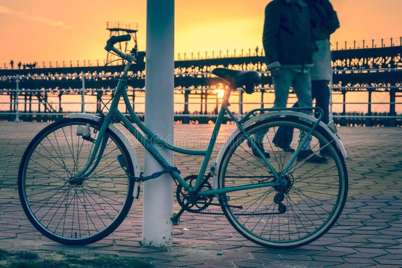 Ένα ζεύγος που περπατά δίπλα σε ένα εκλεκτής ποιότητας ποδήλατο κοντά στην αποβάθρα του Ρίο Tinto Huelva Ισπανία ως ήλιος πηγαίνε στοκ εικόνες