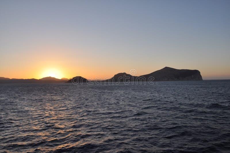 Ένα ζωηρόχρωμο ηλιοβασίλεμα στο λιμάνι Σαρδηνία ΚΌΛΠΩΝ ARANCI στοκ φωτογραφία