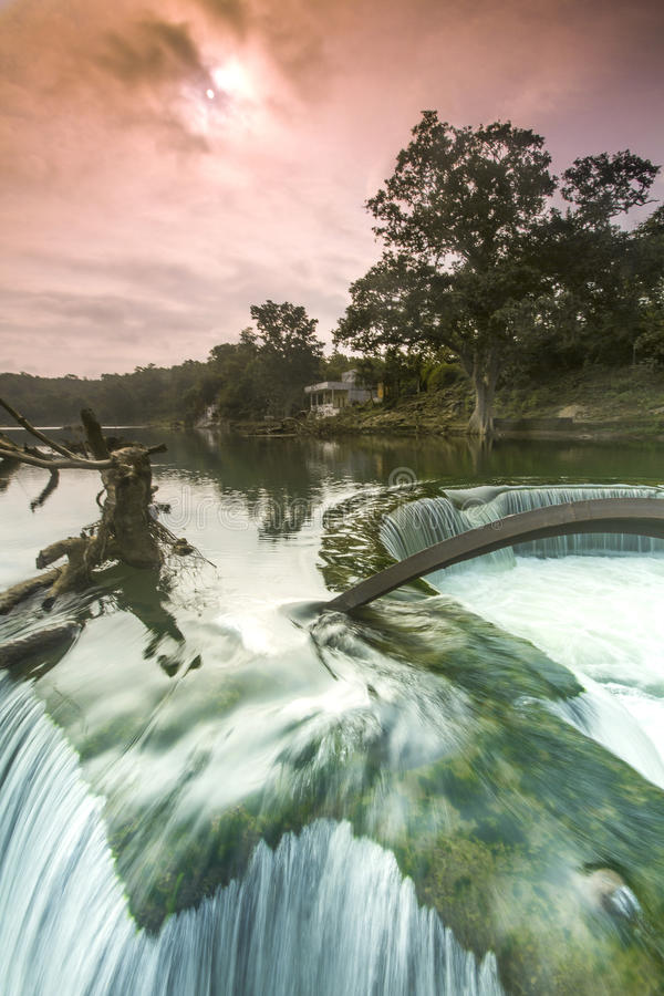Ένα ζωηρόχρωμο υπερφυσικό τοπίο με το πεσμένα δέντρο και το τρεχούμενο νερό στοκ εικόνα